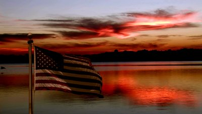 stock-footage-american-flag-flying-at-sunset-over-lake